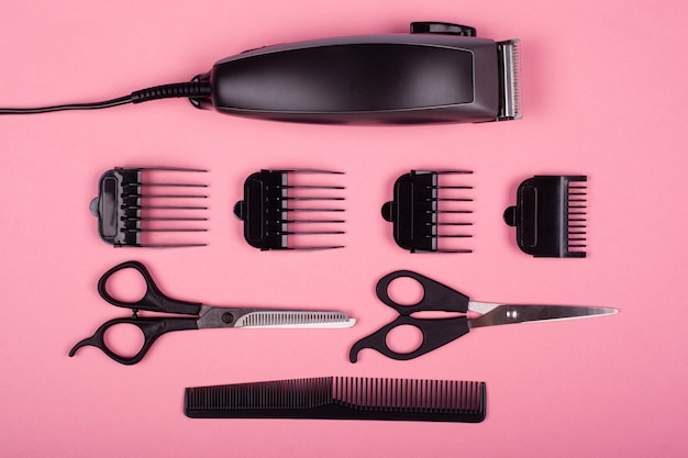 クリッパーとピンクの背景、理髪ツールの櫛とはさみ。