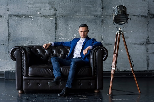 革のソファに座っている青いジャケットの美しいエレガントなファッショナブルな若い男