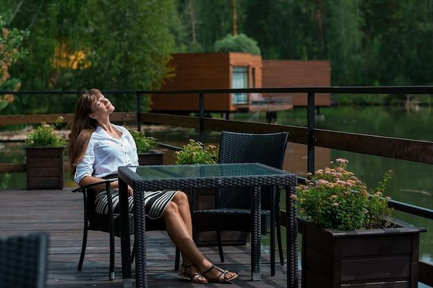 川のそばの夏のカフェで若い美しい女性