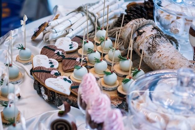Торты и печенье в форме сердечек со словом «любовь» на праздничном столе