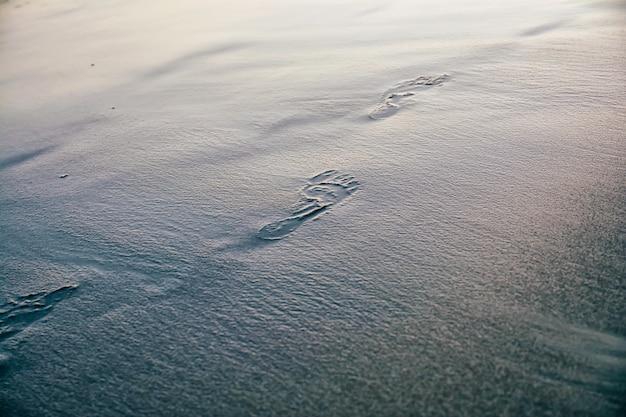 濡れた砂の中の人間の足跡