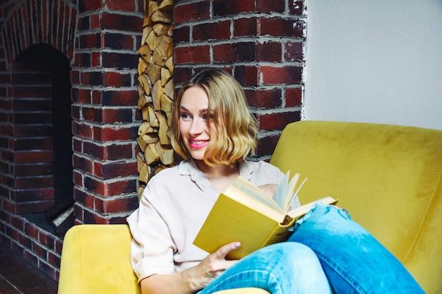 ソファで本を持つ若い美しい女性