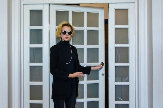Молодая красивая блондинка в черном костюме возле двери