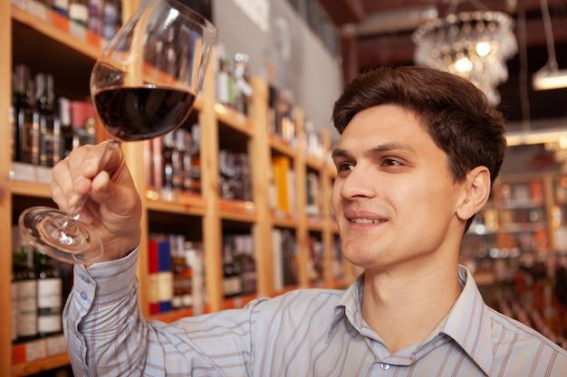 ワインセラーでワインを試飲する陽気な若い男のクローズアップ。幸せな男の手で赤ワインのグラスにセレクティブフォーカス