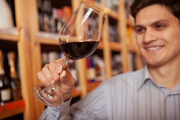 ワイン店で陽気な男の手に赤ワイングラスのクローズアップ。購入前に赤ワインを試飲する幸せな男性客