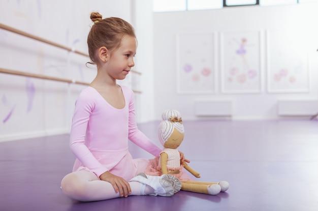 彼女のバレリーナ人形と一緒に床に座って、運動後にバレエ学校で休んでいるピンクのレオタードの魅力的な若いバレリーナ