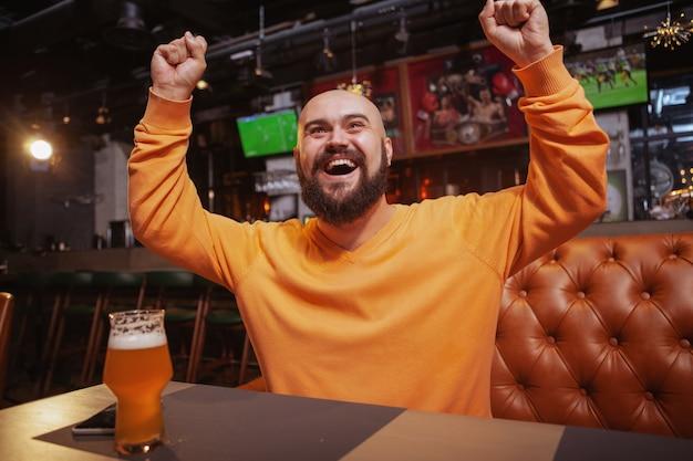 彼のお気に入りのチームの勝利を祝って、ビールのパブでサッカーを楽しく見て叫んでいる幸せな男