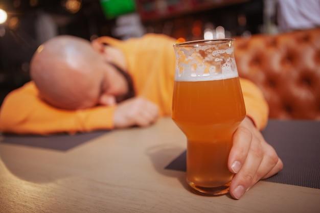 パブで酔った男の手でビールグラスにセレクティブフォーカス。アルコール、中毒、飲酒のコンセプト