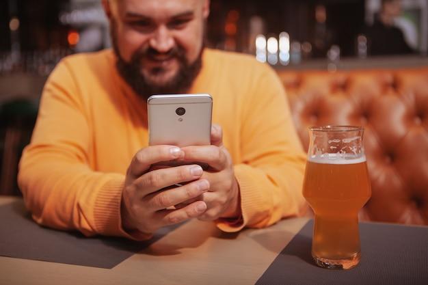 Обрезанный снимок счастливого бородатого мужчины, улыбаясь, используя свой смартфон в пивном пабе
