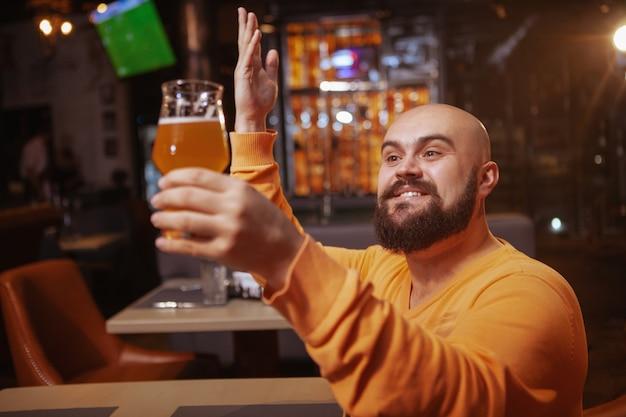 ビールを賞賛するひげを生やした男を興奮させた。彼が保持しているビールグラスを愛で見て幸せな男