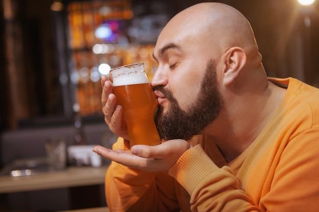 パブで美味しいビールのグラスにキスするひげを生やした男のクローズアップ
