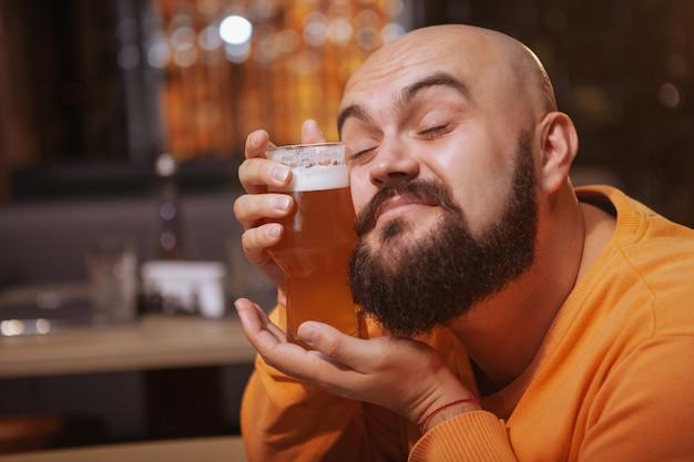 ビールのグラスに寄り添う幸せなひげを生やした男のクローズアップ。彼のビールを愛する陽気な男
