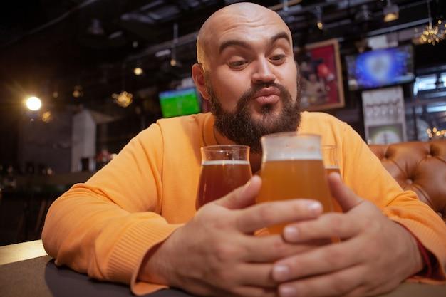 面白いひげを生やした男が彼のビールのグラス、コピー領域に向かってキスを吹いています。アルコール愛、クラフトビールのコンセプト