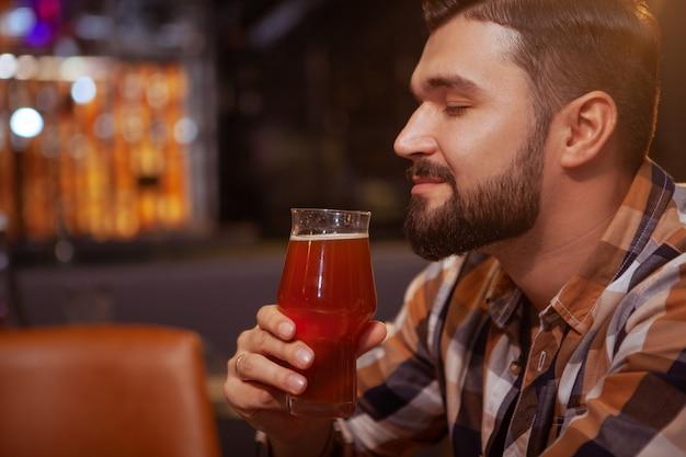 Расслабленный мужчина пахнет ароматом вкусного пива в своем бокале.