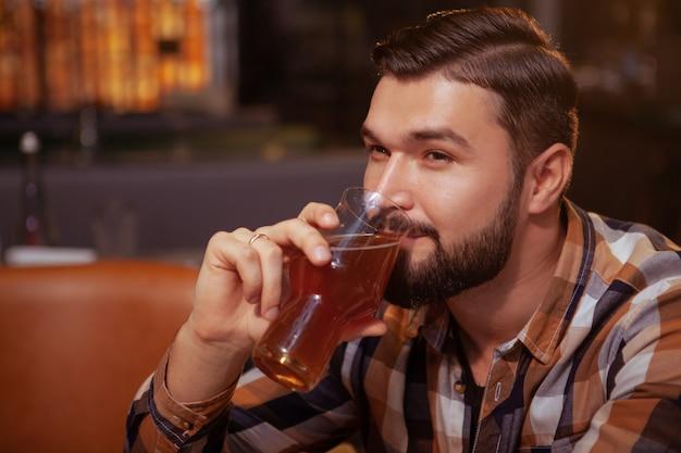Привлекательный бородатый человек, наслаждаясь бокалом пива в пабе