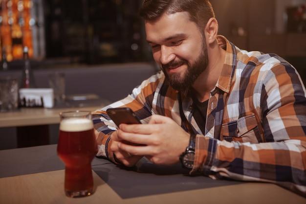 Привлекательный веселый человек, используя свой телефон, попивая пиво в баре