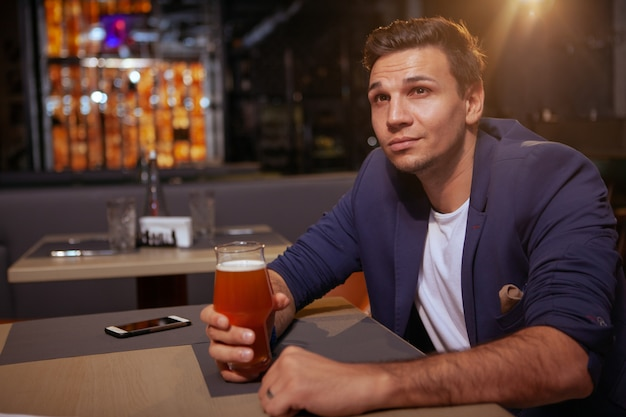 Красивый элегантный молодой человек, наслаждаясь бокалом вкусного пива в пабе, копией пространства