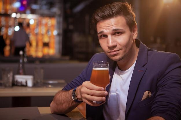 Привлекательный элегантный мужчина, улыбаясь в камеру, наслаждаясь вкусным пивом в пабе