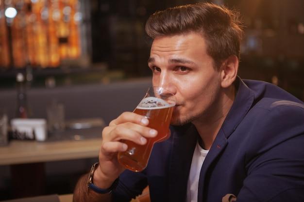 Красивый бизнесмен пьет пиво в пабе, задумчиво глядя в сторону