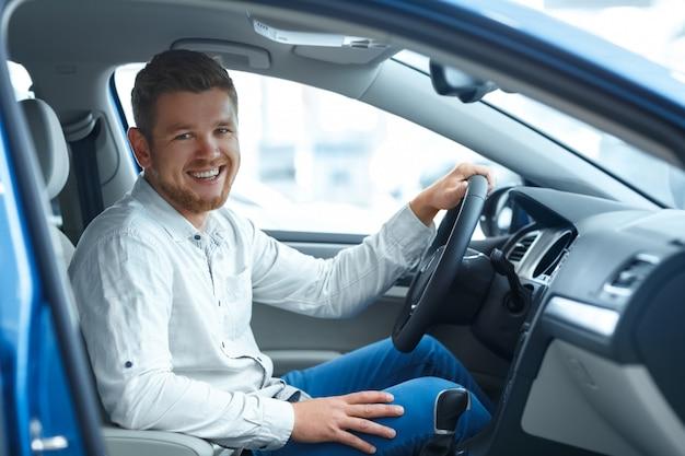 幸せそうに笑って彼の新しい車に座っているハンサムなひげを生やした男の肖像