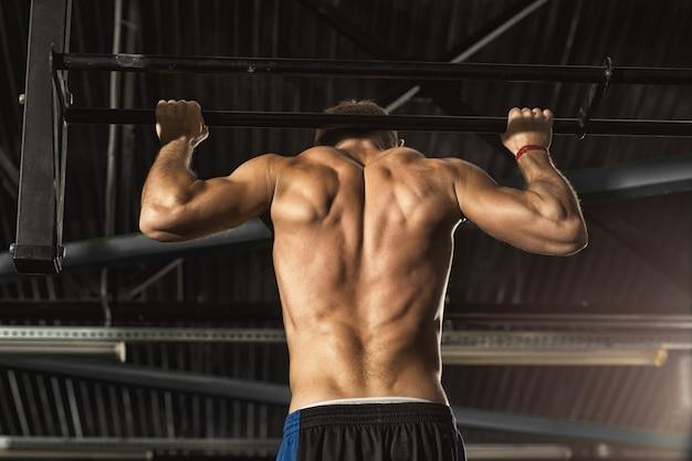 ジムでプルアップを行うワークアウトトーンの筋肉ボディと上半身裸の男