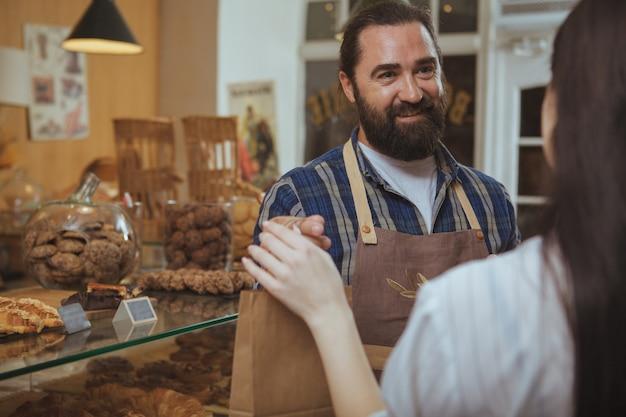 彼の顧客に紙の買い物袋を与えるエプロンを着ているハンサムなひげを生やした成熟したパン屋