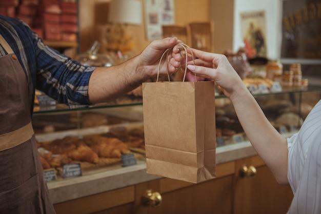 女性客に紙の買い物袋を与えるエプロンを身に着けている男性のパン屋のショットをトリミング