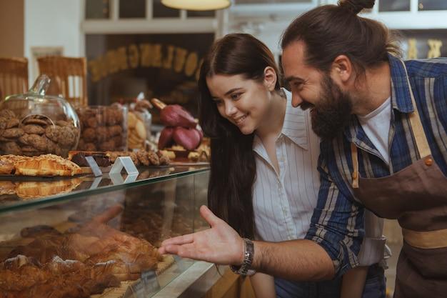 地元のパン屋で焼きたてのおいしいペストリーを買う若い美しい女性