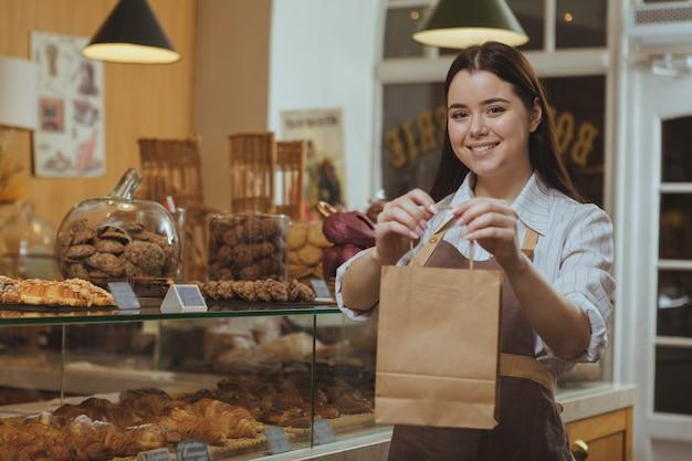 Прекрасная женщина-кондитер продает вкусную еду в пекарне