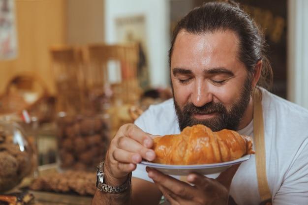 おいしいクロワッサンの臭いがする陽気なひげを生やした男性パン屋の肖像画を間近します。