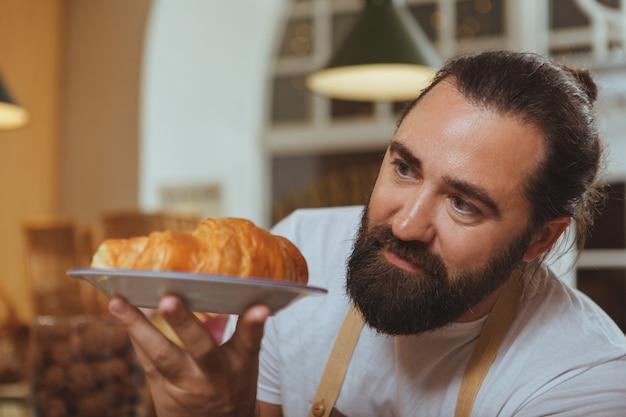 男性のパン屋のひげを生やしたプレートに新鮮なおいしいクロワッサンの選択的な焦点が保持しています。
