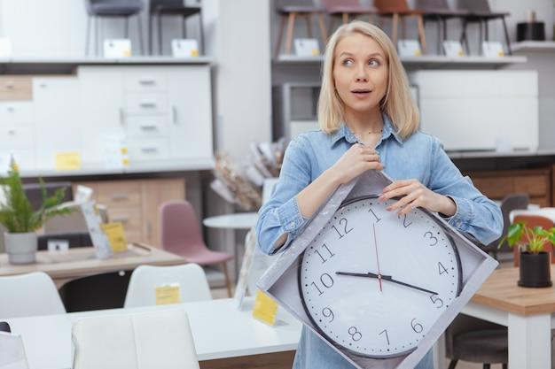 Красивая женщина ищет возбужденных, держа большие настенные часы, покупая товары для дома в универмаге