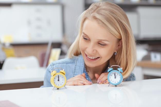 Крупным планом счастливой красивой женщины, улыбаясь, глядя на очаровательны маленький будильник на столе