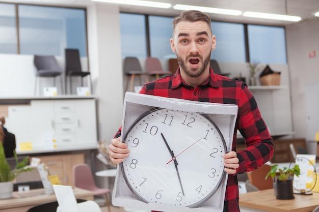 Красивый бородатый мужчина, глядя перегружены, держа большие настенные часы в мебельном магазине