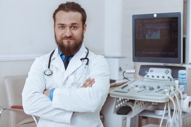Уверенно мужской доктор с гордостью позирует в своей клинике возле ультразвукового сканера