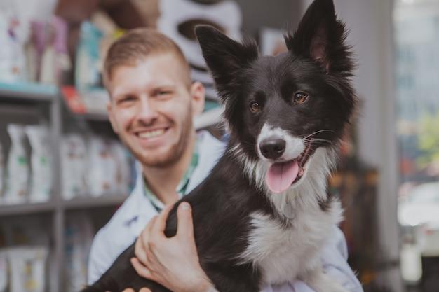 陽気なハンサムな男性獣医によって保持されている光沢のある毛皮を持つ美しい健康な幸せな犬