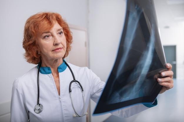 Пожилая женщина-врач осматривает рентген легких пациента