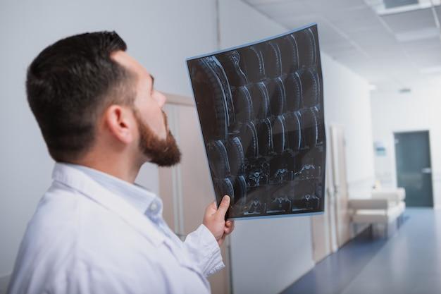 Снимок заднего вида мужского доктора, концентрирующегося, исследующего мрт-сканирование пациента