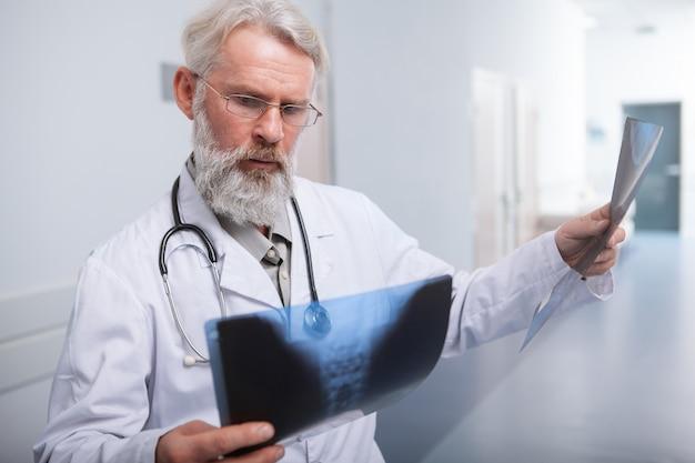 Опытный старший мужчина-врач, выглядящий обеспокоенным, изучает рентгеновские снимки пациента