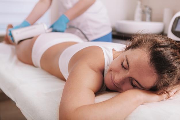 Косметолог, выполняющий подтягивающую кожу процедуру для похудения на клиенте