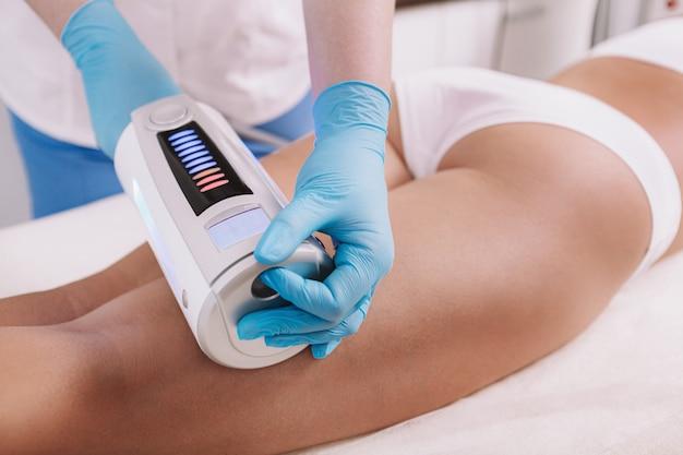 Обрезанный снимок женщины, получающей лечение лепки тела в клинике красоты