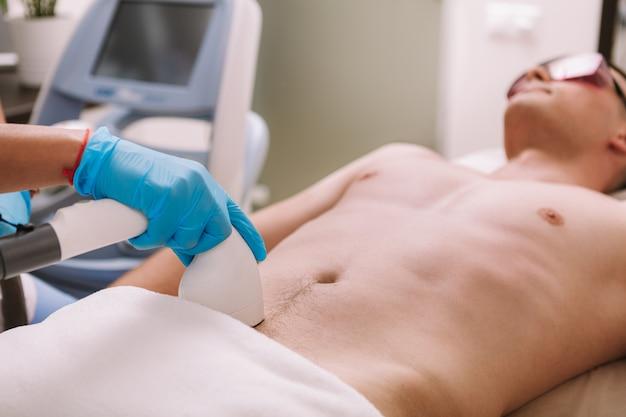 美容師が男性のクライアントの陰毛をレーザーで取り除く。レーザー脱毛治療を受ける人