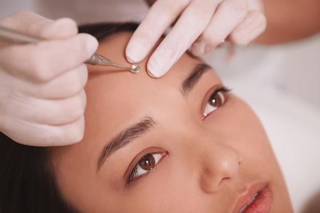 女性のクライアントの顔ににきび除去剤を使用して美容師のクローズアップをトリミング