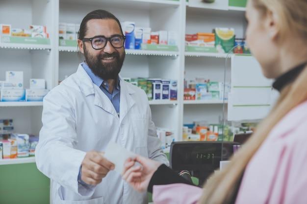 Зрелый бородатый аптекарь работает в аптеке