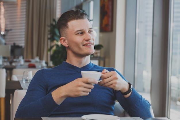 Красивый молодой человек завтракает в кафе