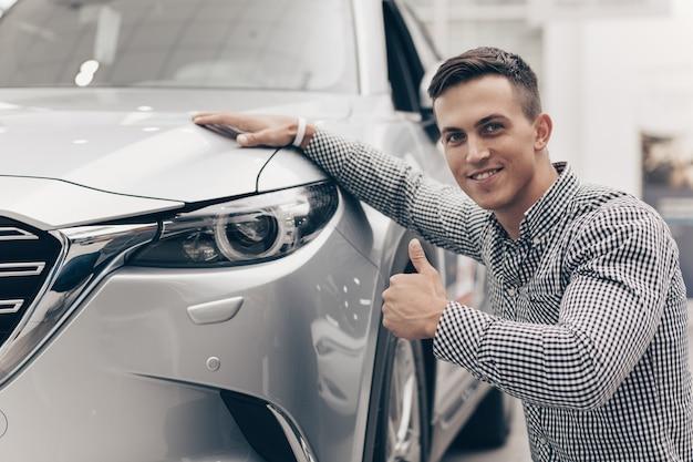 若い男がディーラーで新しい車を買う