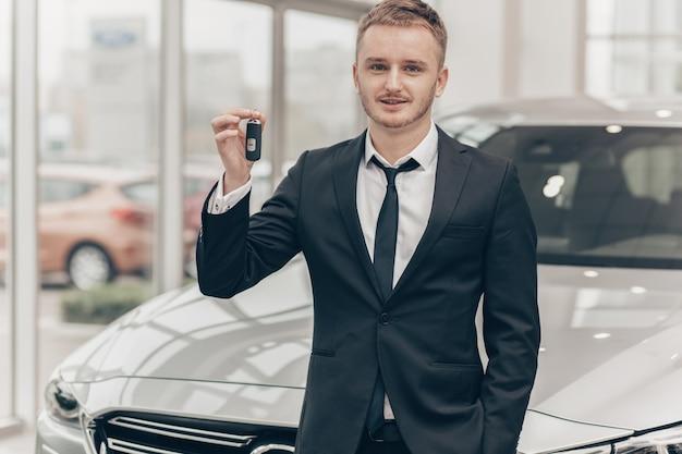 ディーラーで新しい自動車を買う魅力的なビジネスマン