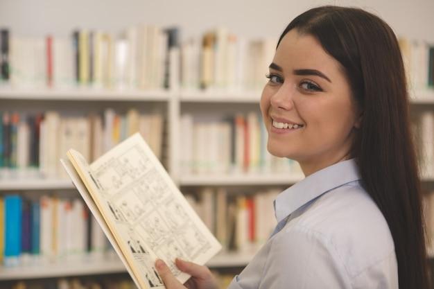 美しい女性の店で本を買い物
