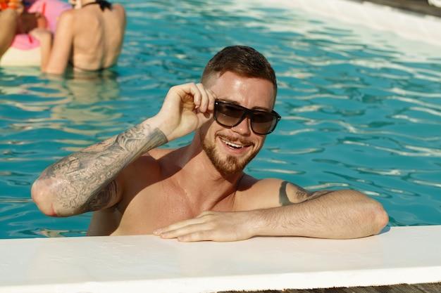 ハンサムな陽気なひげを生やした男のカメラに笑顔のサングラスをかけています。