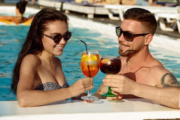 スイミングプールで飲み物を持っている幸せな愛情のある若いカップル。概念